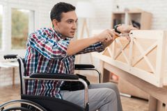 De jonge man in rolstoel probeert zich om zijn boekenkast te vouwen royalty-vrije stock fotografie