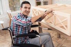 De jonge man in rolstoel probeert zich om zijn boekenkast te vouwen stock fotografie