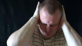 De jonge man sloot zijn oren, die van het luide geluid ontsnappen stock videobeelden