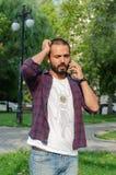 De jonge man spreekt bij zijn celtelefoon bij het park royalty-vrije stock foto's