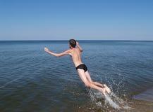 De jonge man springt aan Oostzee Royalty-vrije Stock Afbeeldingen