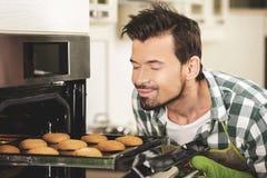 De jonge man trekt de koekjes van de oven royalty-vrije stock foto's