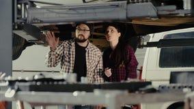 De jonge man verklaart aan zijn collega het meisje, een beginner autowerktuigkundige, de principes van het onderhoud van de autoo stock footage