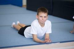 De jonge man voert gymnastiek- oefeningen in het gymnasium uit stock afbeelding