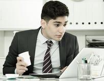 De jonge manager werkt bij een een computer en het drinken koffie stock foto