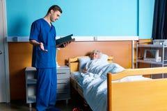 De jonge mannelijke arts bekijkt de analysescores van zijn vrouwelijk klopje stock afbeeldingen
