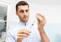 De jonge mannelijke arts bereidt een geneeskunde in de spuit in het bureau voor Arts die een spuit houdt Royalty-vrije Stock Afbeelding
