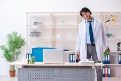 De jonge mannelijke arts die in het bureau drinken royalty-vrije stock fotografie