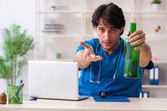 De jonge mannelijke arts die in het bureau drinken royalty-vrije stock afbeelding