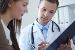 De jonge mannelijke arts houdt een klembord en spreekt met een vrouwelijke patiënt, die in wachtkamer van de kliniek zitten royalty-vrije stock afbeeldingen