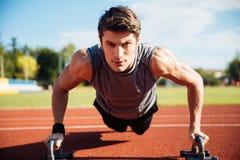 De jonge mannelijke atleet maakt duw UPS op een renbaan Stock Afbeelding