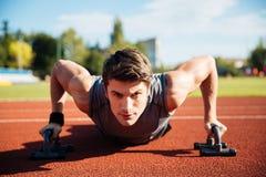 De jonge mannelijke atleet maakt duw UPS op een renbaan Royalty-vrije Stock Foto
