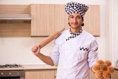 De jonge mannelijke bakker die in keuken werken stock afbeeldingen