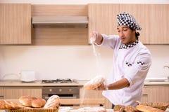 De jonge mannelijke bakker die in keuken werken royalty-vrije stock foto's