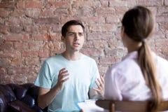 De jonge mannelijke bezoekende adviseur van de psycholoogtherapeut, arts stock afbeeldingen