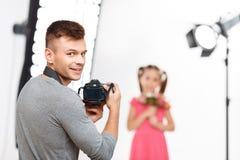 De jonge mannelijke fotograaf glimlacht alvorens te hervatten Stock Afbeeldingen