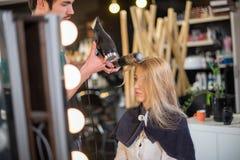 De jonge mannelijke kapper droogt meisjeshaar royalty-vrije stock fotografie