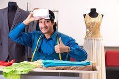 De jonge mannelijke kleermaker die op workshop werken stock foto