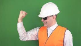 De jonge mannelijke leider in een signaalvest en een beschermende helm, zwarte glazen, verheugt zich bij het ondertekende bouwcon stock videobeelden
