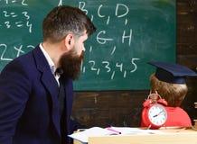 De jonge mannelijke leraar begeleidt zijn kindstudent aan het leren terwijl de zoon bord met gekrabbel bekijkt, aanwezig zijnd stock foto's
