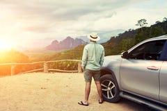 De jonge mannelijke reiziger geniet van mooi landschap tijdens wegreis op suv in Thailand Stock Foto