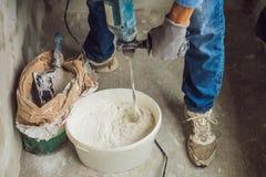 De jonge mannelijke schilder kneedt stopverf met water in een emmer gebruikend een handbediende mixer voor de bouw van mengelinge royalty-vrije stock foto