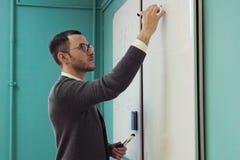 De jonge mannelijke spreker schrijft op whiteboard in klaslokaal Royalty-vrije Stock Foto's