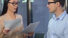 De jonge mannelijke stagiair die goedkeuring van baan van businesslady krijgen, plaatst in bedrijf stock video