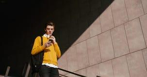 De jonge mannelijke tiener is geconcentreerd op zijn mobiele telefoon terwijl het gaan onderaan de treden De jeugd en technologie stock video