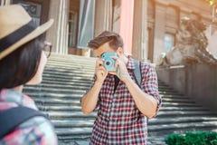 De jonge mannelijke toeristentribune bij stappen en neemt beelden van vrouw Hij houdt blauwe camera in handen De mens is ernstig  royalty-vrije stock fotografie