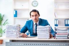De jonge mannelijke werknemer ongelukkig met het bovenmatige werk royalty-vrije stock foto's