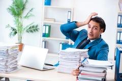 De jonge mannelijke werknemer ongelukkig met het bovenmatige werk stock afbeeldingen