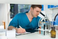 De jonge mannelijke wetenschapper in eenvormig kijkt door een microscoop stock fotografie