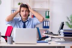 De jonge mannelijke zakenmanwerknemer ongelukkig met het bovenmatige werk stock afbeelding