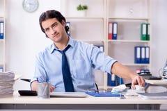 De jonge mannelijke zakenmanwerknemer ongelukkig met het bovenmatige werk stock fotografie