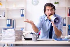 De jonge mannelijke zakenmanwerknemer ongelukkig met het bovenmatige werk royalty-vrije stock foto