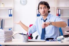 De jonge mannelijke zakenmanwerknemer ongelukkig met het bovenmatige werk stock foto