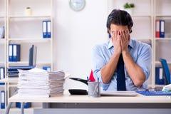 De jonge mannelijke zakenmanwerknemer ongelukkig met het bovenmatige werk royalty-vrije stock afbeeldingen