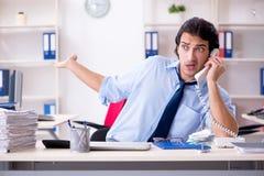 De jonge mannelijke zakenmanwerknemer ongelukkig met het bovenmatige werk stock afbeeldingen