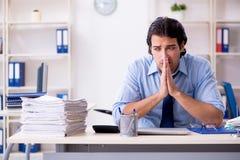 De jonge mannelijke zakenmanwerknemer ongelukkig met het bovenmatige werk royalty-vrije stock fotografie