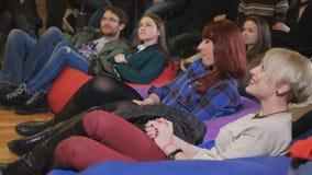 De jonge mannen en de vrouwen die op de komedie lachen tonen stock video