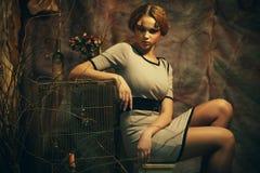 De jonge mannequin met creatief maakt omhoog het zitten op een kruk Royalty-vrije Stock Foto