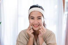 De jonge massage van het vrouwen zelfgezicht stock fotografie