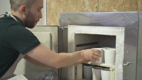 De jonge meester zet kleiproducten in de workshop van het ovenaardewerk stock videobeelden