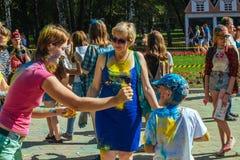 De jonge meisjes en de jongens nemen aan Holi-kleurenfestival deel Stock Afbeelding