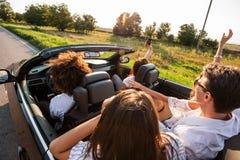 De jonge meisjes en de kerels zitten in een zwarte convertibele auto en maken foto op de telefoon bij zonsondergang stock afbeelding