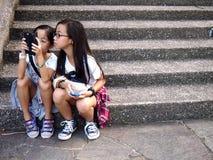 De jonge meisjes gebruiken hun cellphone of smartphone terwijl het zitten bij een trap in Tampines, Singapore Royalty-vrije Stock Foto's