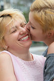 De jonge meisjes kussende moeder stock fotografie