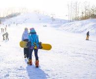 De jonge meisjes in speciale kostuums voor de winterpret en de wintersporten beklimmen de heuvel om hoe te snowboard op een zonni stock foto