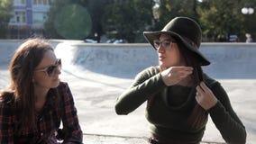 De jonge meisjes zitten in de herfst in het park en communiceren stock footage
